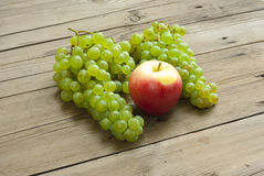 Apples and grapes on wooden table Stock Images