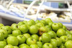 Apples are green in the shop window. Transparent showcases in the background. stock photos