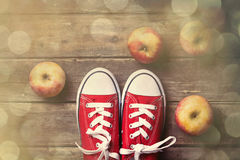 Apples and gumshoes. Photo of the delicious apples and red gumshoes on the brown wooden background. Photo im old color image style with bokeh Royalty Free Stock Photo