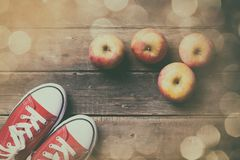 Apples and gumshoes. Photo of the delicious apples and red gumshoes on the brown wooden background. Photo im old color image style with bokeh Royalty Free Stock Photography