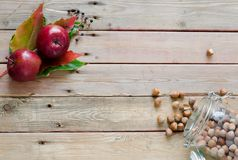 Apples and hazelnuts on wooden background. Apples and hazelnuts with autumn leaves on wooden background Stock Photography