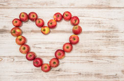 Apples in heart shape on wooden background. Love concept Stock Photo