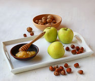 Apples, honey and nuts on a white tray Stock Photo