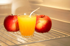 Apples and juice in empty refrigerator. Conceptual idea: couple apples and natural juice in empty refrigerator - good food for diet Stock Photos