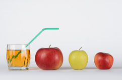 Apples and juice in glass. Green, red apples with apple juice in he glass on white background Royalty Free Stock Photo
