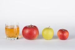 Apples and juice in glass. Green, red apples with glass of apple juice on white background Royalty Free Stock Photo