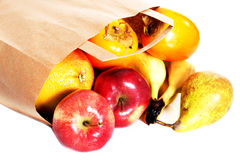 Apples,kaki and pears lying on the floor in paper bag. Stock Photos