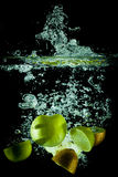 Apples and kiwis water splash. On black background stock photography