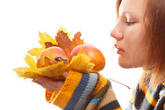 Apples and leaves. Beautiful young woman in striped sweater holding autumn leaves and apples isolated on white background royalty free stock photos