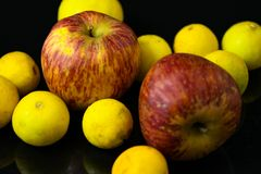 Apples and lemons on black background royalty free stock photography