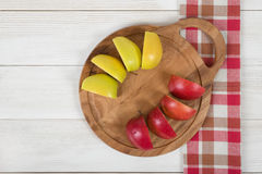 Apples lie on a wooden board and checkered kitchen tablecloth in top view. Table decoration. Healthy food. Improving health. Beating diarrhea and constipation Stock Images