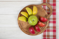 Apples lie on a wooden board and checkered kitchen tablecloth in top view. Table decoration. Healthy food. Improving health. Beating diarrhea and constipation Stock Photography