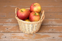 Apples in light brown wicker basket on old wooden desk closeup Royalty Free Stock Images