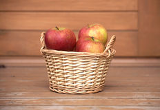 Apples in light brown wicker basket on old wooden desk closeup Stock Image