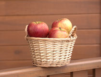Apples in light brown wicker basket on wooden fence Stock Photos