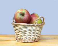 Apples in light brown wicker basket on wooden table Royalty Free Stock Photo