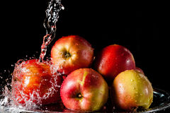 The apples lying on a silver top and falling water Stock Photos