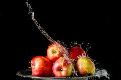 The apples lying on a silver top and falling water Stock Images