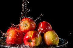 The apples lying on a silver top and falling water Royalty Free Stock Image