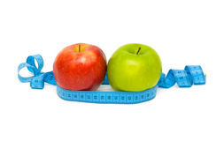 Apples and measuring tape on white background. Red and green apples and measuring tape on white background Royalty Free Stock Images