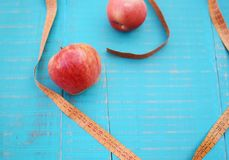 Weight loss concept. Apples and measuring tape on wooden background Royalty Free Stock Photo