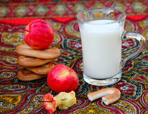 Apples and Milk. Organic apples, russian bagels sushki and    mug of milk on colorful tablecloth Stock Images