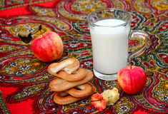 Apples and Milk. Organic apples, russian bagels sushki and    mug of milk on colorful tablecloth Stock Photo