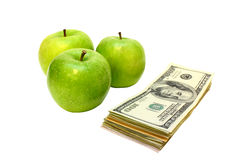 Apples and money. Three green apples and stack of money isolated on a white background Stock Image