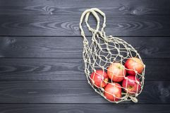 Apples in natural hemp string bag on a dark wooden background. copy space royalty free stock photos