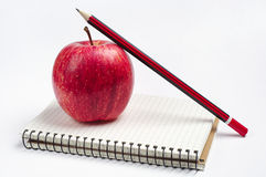 Apples, notebook and pencil Royalty Free Stock Photos