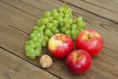 Apples , nut and grapes on wooden table Royalty Free Stock Images