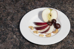 Apples and Nuts. Arrangement of apples and nuts on a white plate Royalty Free Stock Photos