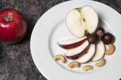 Apples and Nuts. Arrangement of apples and nuts on a white plate Royalty Free Stock Photo