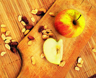 Apples and nuts on a cutting board Stock Images
