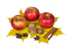 Apples, nuts and spices in autumn maple leaves royalty free stock photography