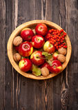 Apples and nuts in wooden bowl Stock Photography