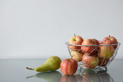 Apples in openwork metal vase and pear on a glass table. Apples in openwork metal vase and pear standing on a glass table Royalty Free Stock Images