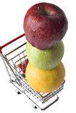 Apples and an orange in a miniature shopping cart Stock Images