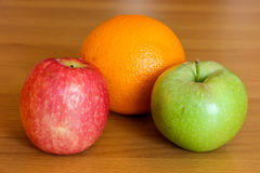 Apples and orange on table Royalty Free Stock Photo