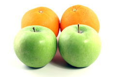 Apples and oranges. Two green granny smith apples and two oranges on a white background Stock Image