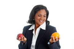 Apples and Oranges. Woman comparing apples and oranges on a white background Stock Image
