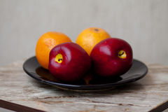 Apples with oranges. On black plate Royalty Free Stock Photos