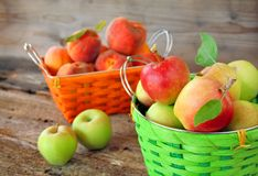 Apples and Peaches. A basket of apples and a basket of peaches with a rustic surrounding.  Focus is on the basket of apples Stock Photography