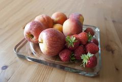 Apples, peaches and strawberries on on glass serving plate on the wooden table close up. Concept of harvest. New apples season. Concept of autumn. Concept of royalty free stock photos