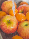 Apples and peaches are washed in the sink. stock photos