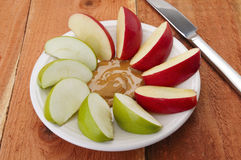 Apples and peanut butter. Organic peanut butter and organic apple wedges green and red spread out on a white plate which sits on a redwood picnic table Royalty Free Stock Photos