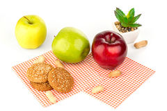 Apples, peanuts and oatmeal cookies on a white table. Apples, peanuts, oatmeal cookies and aloe flower Stock Photography