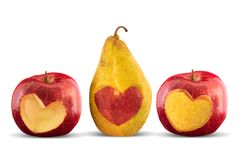Apples and pear with heart shape carved out on white background. Two apples and one pear with heart shape carved out, on white background Royalty Free Stock Photo