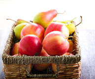 Apples and pears. In a basket on table Stock Images