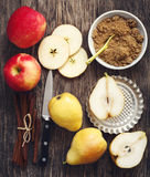 Apples, pears, cinnamon sticks and brown sugar on wooden background Royalty Free Stock Image